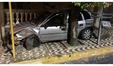 Motorista perde o controle da direção, carro sobe em calçada e fica preso entre muro e árvore