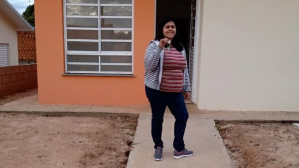 Com a chave na mão recebida nesta semana, em frente à tão esperada casa própria, Priscila Machado é uma das novas moradoras do lugar (Cedida).