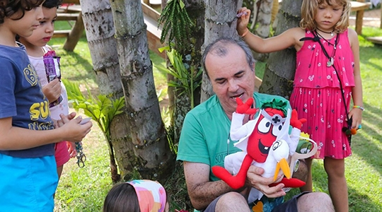O escritor Sergio Paiollo em atividades de contação de histórias com os personagens do seu novo livro Tomatinho Tom e o mundo além dos muros (Imagens: Divulgação).