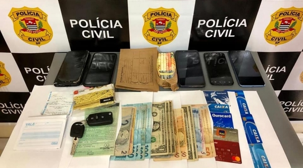 Dinheiro, celulares e outros materiais apreendidos pela Polícia Civil com o trio paranaense, em Adamantina (Foto: Cedida/Polícia Civil).