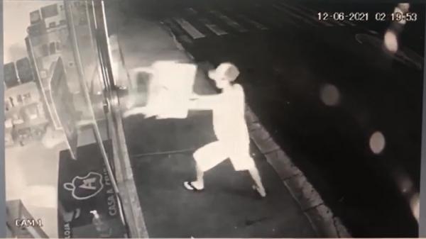 Assaltante arremessa uma antiga carteira escolar contra a porta de vidro, por duas vezes, na tentativa de furto (Cedida).