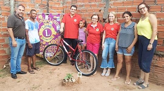 Companheiros do Lions Clube, educadores da EMEF Prof. Eurico Leite de Morais e aluna Jéssica recebendo a bicicleta ao lado de seus familiares (Foto: Assessoria de Imprensa/Lions Clube de Adamantina).