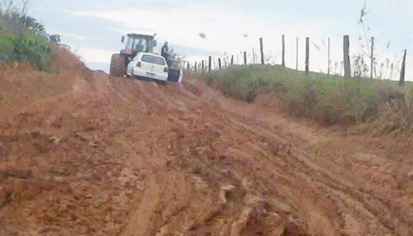 Trator rebocando carro devido o atoleiro na estrada (Foto: Reprodução/Facebook).