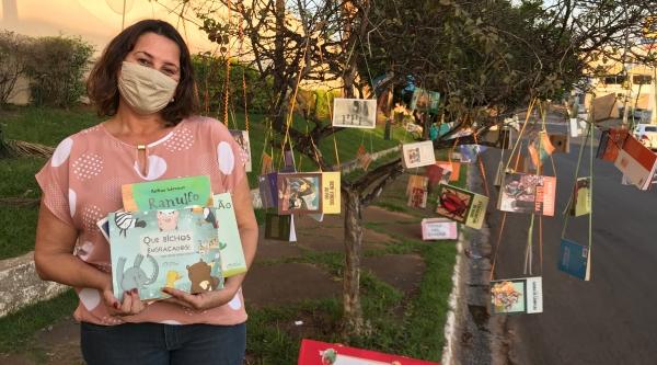 Ana Luiza Cordeio com as árvores de livros, na Avenida Rio Branco (Foto: Siga Mais).