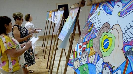 Artistas plásticas Áurea Andrade, Aureni Luiz e Nonuvia Vasques avaliando os cartazes (Da Assessoria).